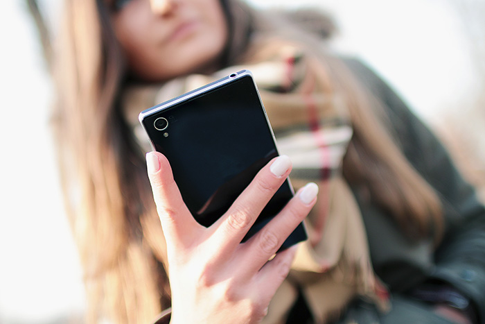 A young woman holds a smartphone in her hand